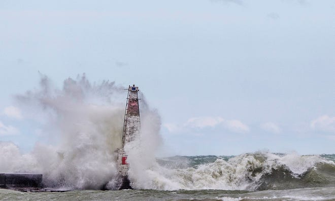 In this April 6, 2017 file photo, big waves crash against a breakwater light as strong winds create dangerous conditions on Lake Michigan, at Washington Park in Michigan City, Ind.