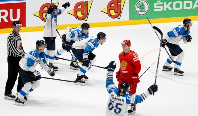 Russia's Nikita Gusev skates past Finland players as they celebrate their 1-0 win in Saturday's semifinal.