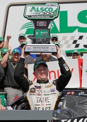 Tyler Reddick raises the trophy after winning the NASCAR Xfinity Series race at Charlotte Motor Speedway on Saturday.