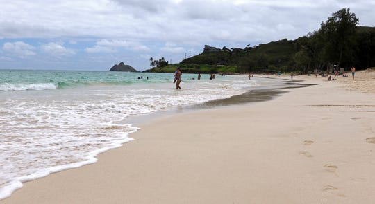 In this May 15, 2019, photo, people stand near the ocean at Kailua Beach Park in Kailua, Hawaii.