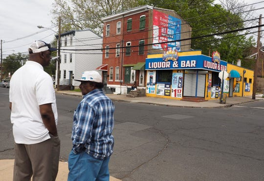 Local residents stand across the street from Ramoneros Liquor & Bar in Trenton, N.J., Saturday, May 25, 2019.