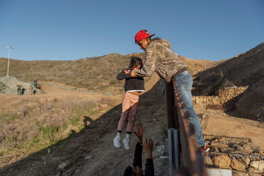 A migrant from Honduras passes a child to her father after he jumped the border wall to get into the U.S. side to San Diego, Calif., from Tijuana, Mexico, on Jan. 3.