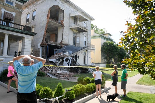 Neighbors and bystanders view the damage to a home under renovation at 414 S.E. Riverside after a truck hit the home around midnight Friday night.