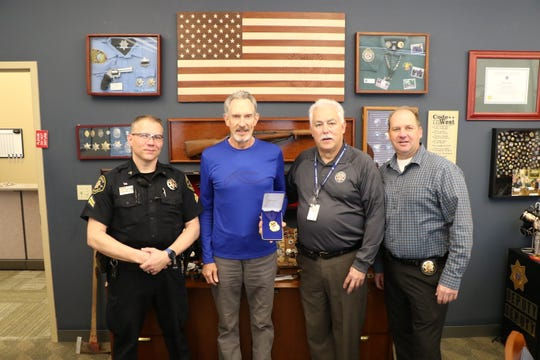 Rob Harrison (middle left) was awarded the Larimer County Sheriff's Office Sheriff's Star award for assisting deputies in saving an injured, suicidal woman in May 2018. Harrison is pictured receiving the award from Undersheriff Nelson, Captain Loberg and Corporal Wicker.