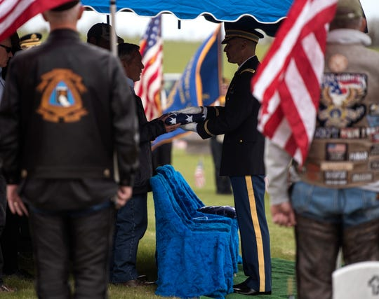 The honor guard presents Don McHenry, Pvt. William A. Boegli's eldest nephew, with a folded flag on Saturday, May 25, 2019, at Sunset Hills Cemetery in Bozeman, Mont. (Rachel Leathe/Bozeman Daily Chronicle via AP)