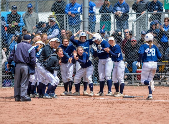 Great Falls High's Rachel Porter greeted by teammates at home after hitting a go ahead two-run homerun in the first game of the championship round of the Class AA state softball tournament on Saturday in Butte.