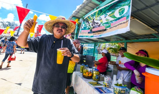 "Danny Charfauros delivers his best sales pitch to promote sales of homemade mango popsicles and ""mangomade"" at his family-operated Fresko vendor stall during the 13th annual Agat Mango Festival May 25."