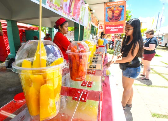 California resident Charlene Lava, right, places an order for mangonada juice during her first visit to the 13th annual Agat Mango Festival on Saturday, May 25, 2019. The fair, which opened on Friday night, is scheduled to continue on Sunday, starting at 10:00 a.m. and culminating with a fireworks display slated for 10:00 p.m. in the evening.