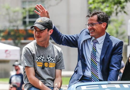 IMS President J. Douglas Boles, his son Carter, and wife Beth, not shown, wave to fans during the annual IPL 500 Festival Parade through downtown Indianapolis on Saturday, May 25, 2019.