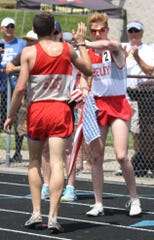 Shelby's Caleb Brown congratulates a relay teammate in last year's Division II regional track meet at Lexington