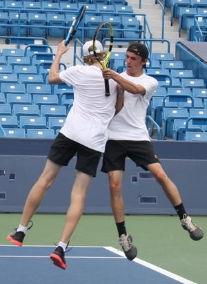 Lexington's Benton Drake and Blake Webster celebrate winning a point while playing on Center Court in the Lindner Family Tennis Center at the state high school tennis tournament.
