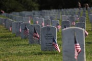 Volunteers plant flags on the 18,000 headstones in honor of Memorial Day at the West Tennessee State Veterans Cemetery on Saturday, May 25, 2019.