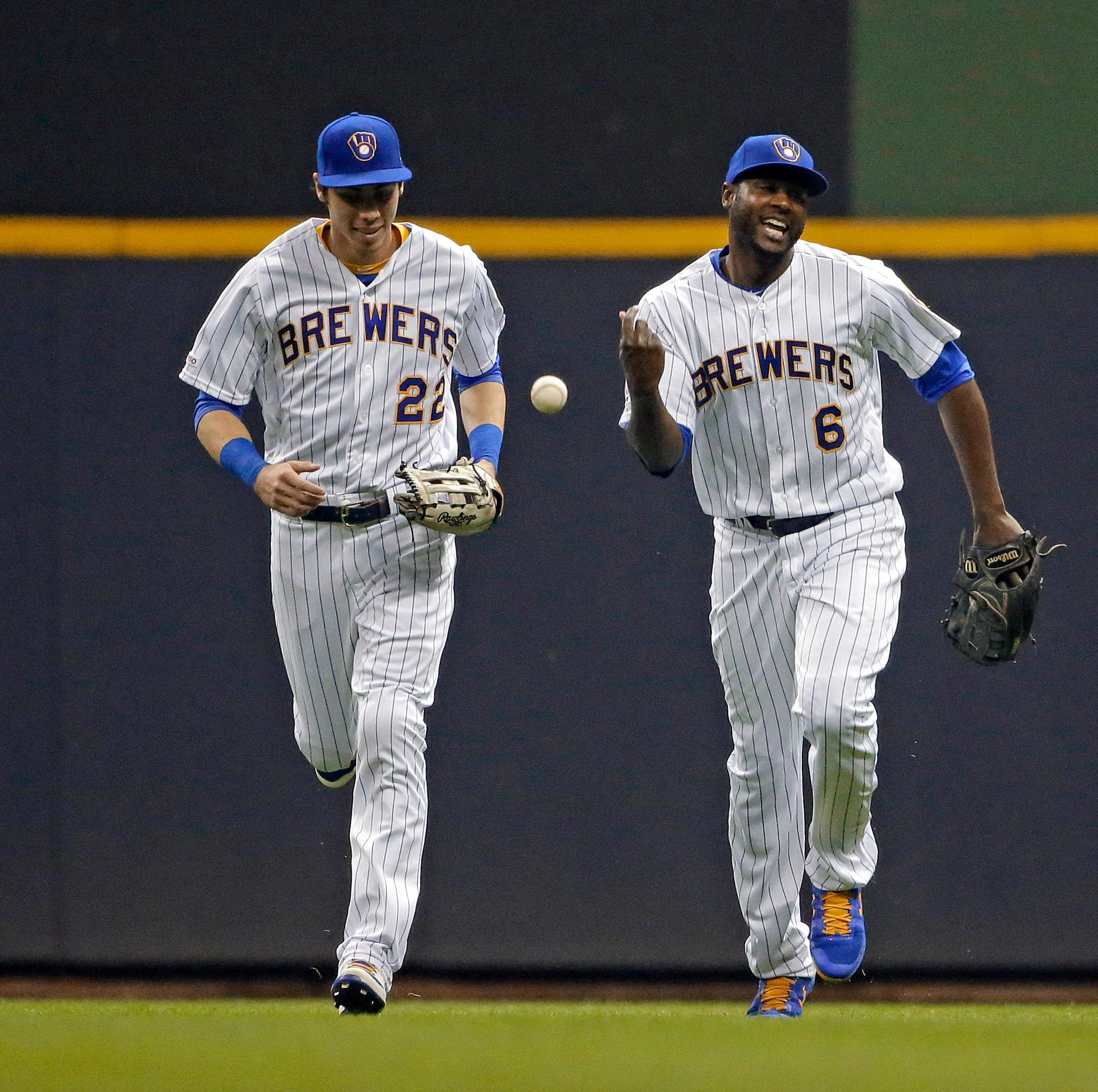 The Brewers' Lorenzo Cain (right) smiles with...
