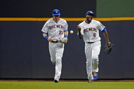 The Brewers' Lorenzo Cain (right) smiles with Christian Yelich after making a catch at the wall to end the fifth inning.
