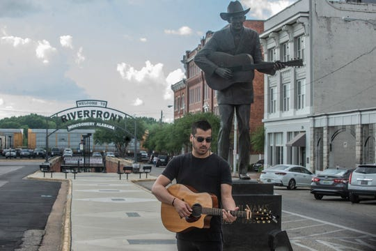 Country artist Michael Zaib breaks out his guitar in downtown Montgomery alongside the statue of Hank Williams.