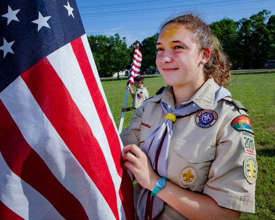 Mackenzie Neal of Scouts BSA Troop 2019 unfurls a flag during the 2019 Healing Fields event in Murfreesboro over Memorial Day weekend.