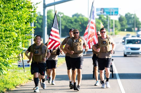 Shepherd's Men run down Gallatin Pike Saturday, May 25, 2019, in Nashville, Tenn. The runs are each 22 kilometers and they wear 22 pound vests, representing the 22 suicide deaths that occur among U.S. veterans per day, according to the Shepherd's Men website.