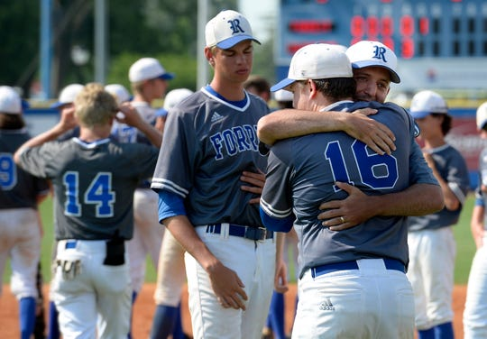 Forrest players and coaches comfort each other after team's loss to Covington in the TSSAA Class AA  championship game Friday, May 24, 2019, in Murfreesboro, Tenn.
