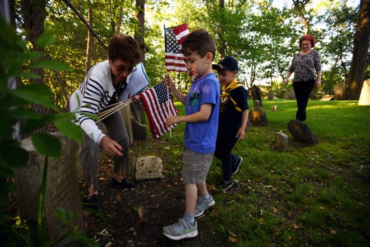 Matthew Colangelo, a Cub Scout with Troop 78, places a flag at a gravestone during a flag ceremony at the French Huguenot - Demarest Cemetery in New Milford on Friday, May 24, 2019. (left) Darlene Minko, Chairperson of the Public Events Committee.