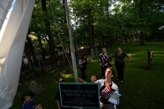 Darlene Minko, Chairperson of the Public Events Committee, lowers a flag before the start of a flag ceremony at the French Huguenot – Demarest Cemetery in New Milford on Friday, May 24, 2019.