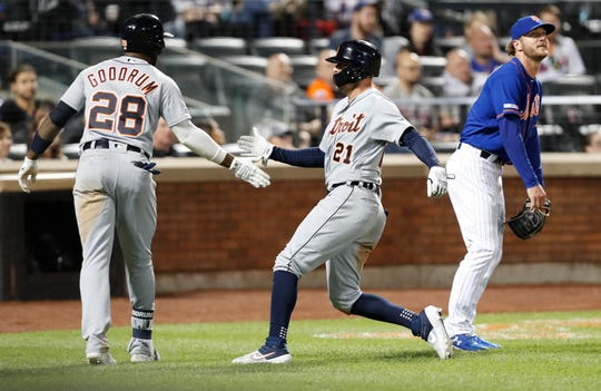 Detroit Tigers on-deck batter Niko Goodrum (28) greets teammate JaCoby Jones (21) after Jones scored on Brandon Dixon's pinch-hit RBI-single during the seventh inning of a game against the New York Mets, Friday, May 24, 2019, in New York. Mets relief pitcher Drew Gagnon, right, looks on.
