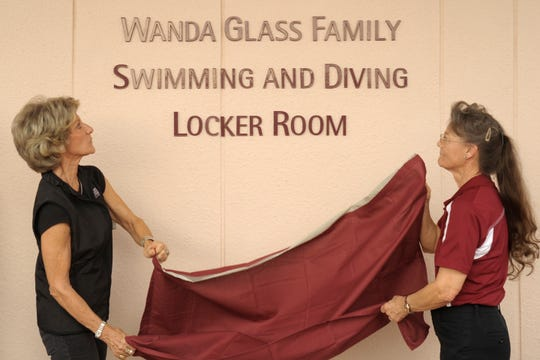 Sisters Smoky Glass Torgerson, left, and Linda Glass Schroeder unveil the sign for the new Wanda Glass Family Swimming and Diving Locker Room at the NMSU aquatic center outdoor pool during a special ribbon-cutting event.