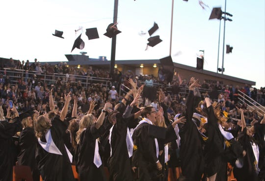 Aztec High School graduates toss their caps into the air.