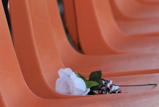 A white rose on an empty chair memorializes students who died before they could graduate.