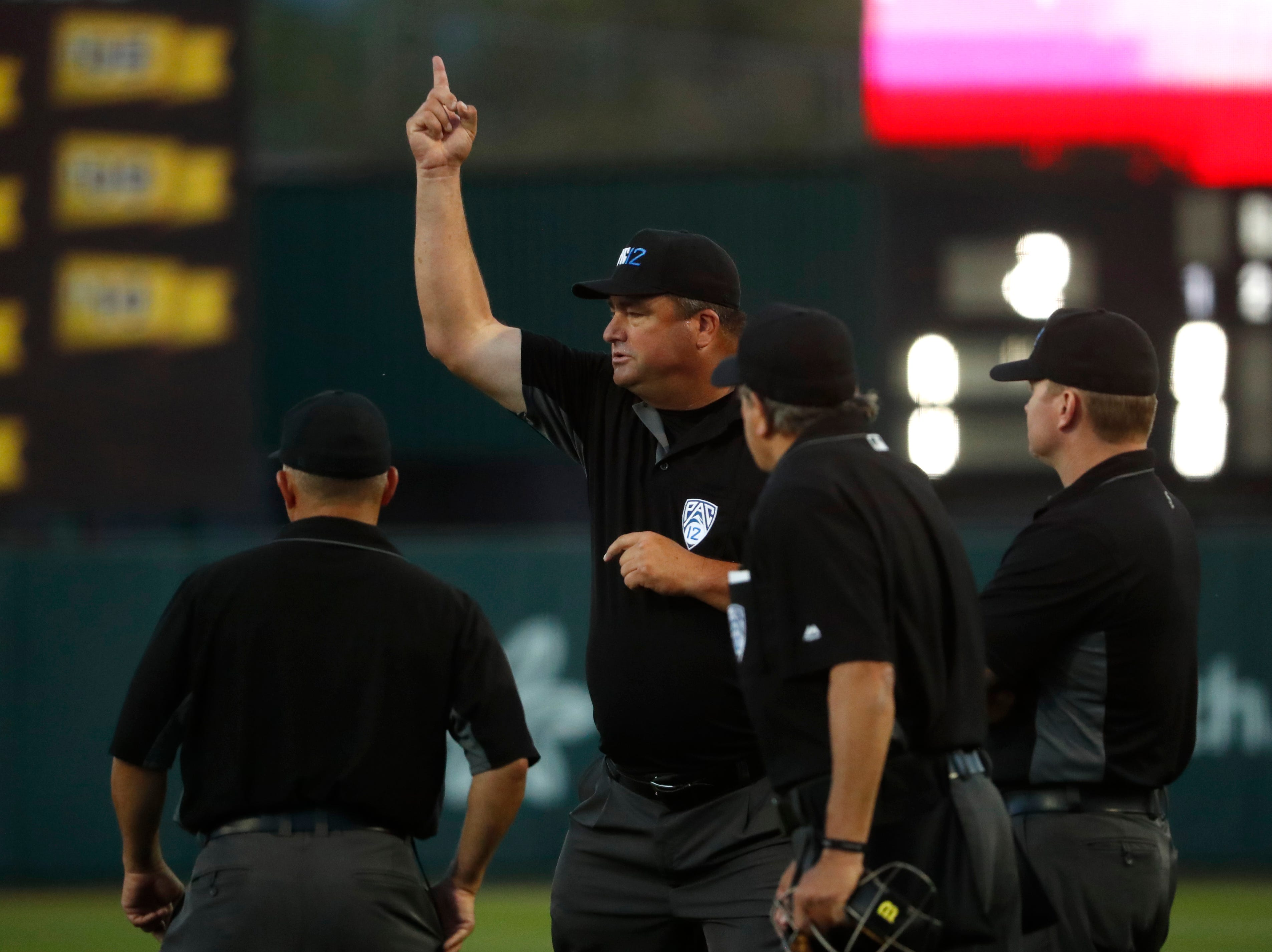 After a visit, home plate umpire Joe Burleson signals to change ASU's Carter Aldrete's double to a home run during the sixth inning at Phoenix Municipal Stadium in Phoenix, Ariz. on May 24, 2019.