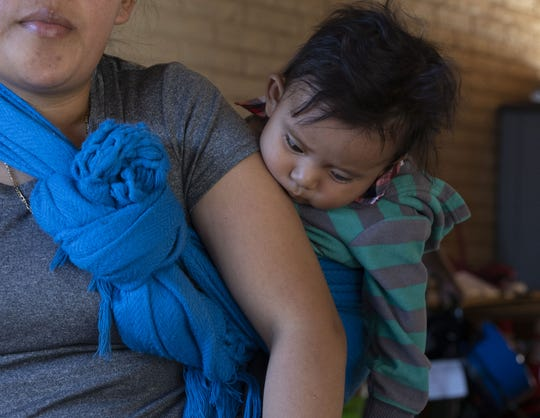 A baby is shown in a sling-style carrier at Iglesia Cristiana El Buen Pastor church in Mesa on May 24, 2019.