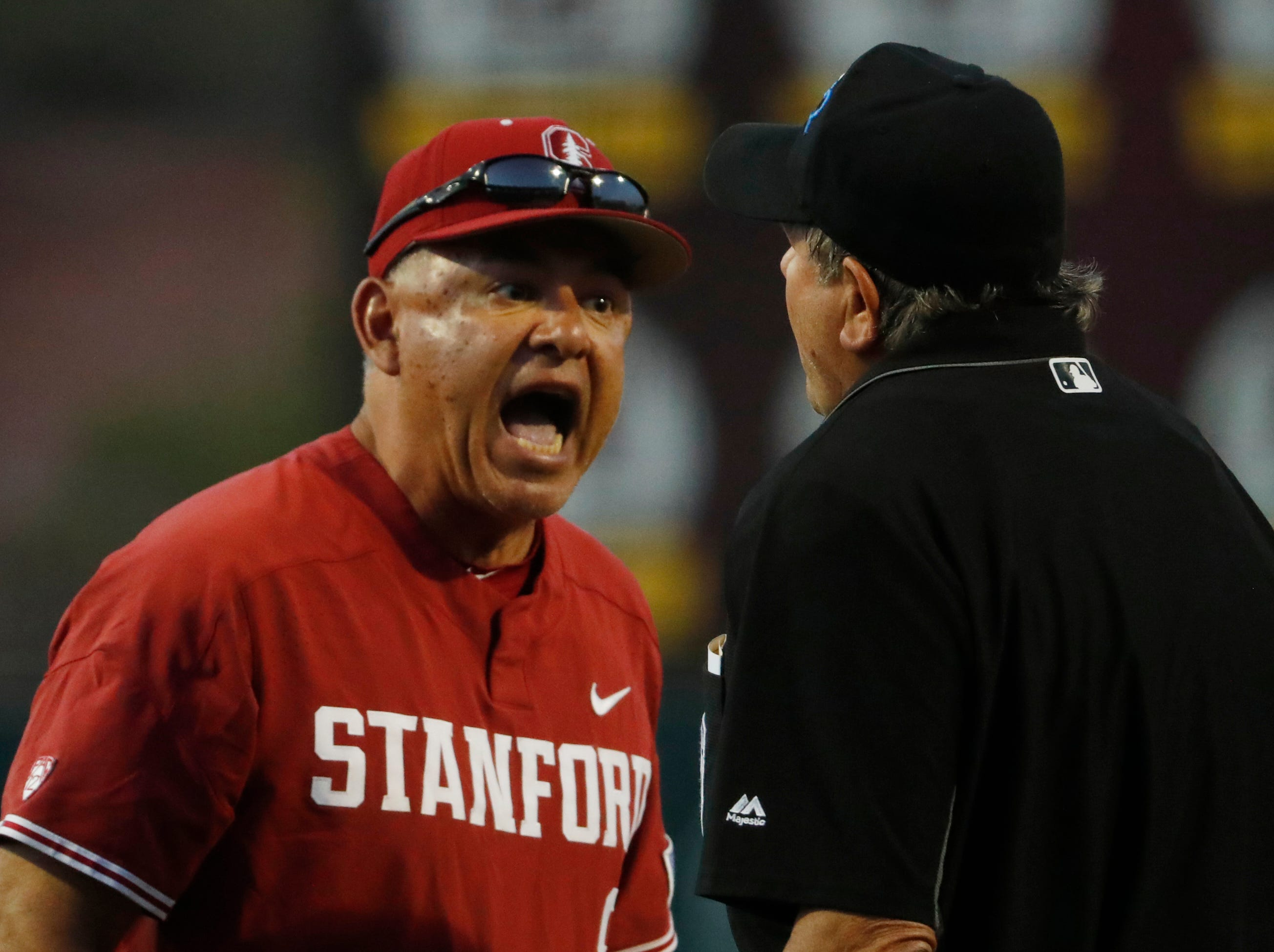 Stanford's head coach David Esquer argues with home plate umpire Joe Burleson after a ground rule double was changed to a home run during the sixth inning at Phoenix Municipal Stadium in Phoenix, Ariz. on May 24, 2019.
