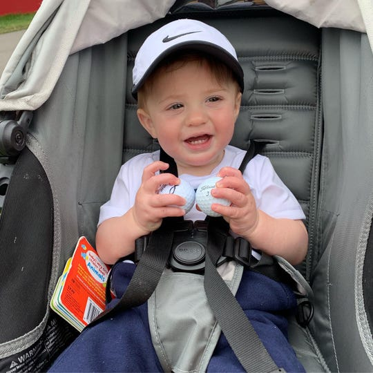 Jake Zaruta, 11 months, of Henrietta holds on to golf balls that were given to him by Billy Andrade and Lee Janzen at the Senior PGA Championship on Saturday. Jake, who is the son of Doug and Brittany Zaruta, was attending the first sporting event of his life.