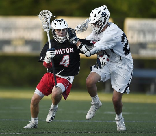 Hilton's Matthew Mojsej, left, is defended by Pittsford's Nathan Strauf during a Class A sectional semifinal at Webster Thomas High School, Friday, May 24, 2019. No. 3 seed Hilton advanced to the Class A final with an 8-7 overtime win over No. 2 seed Pittsford.