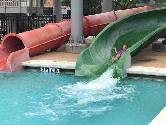 Ella Highsmith goes down a green slide at Municipal Pool Saturday, May 25, 2019.