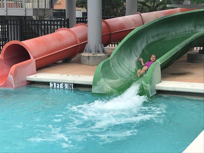 Ella Highsmith goes down a green slide at Municipal Pool Saturday, May 25, 2019.