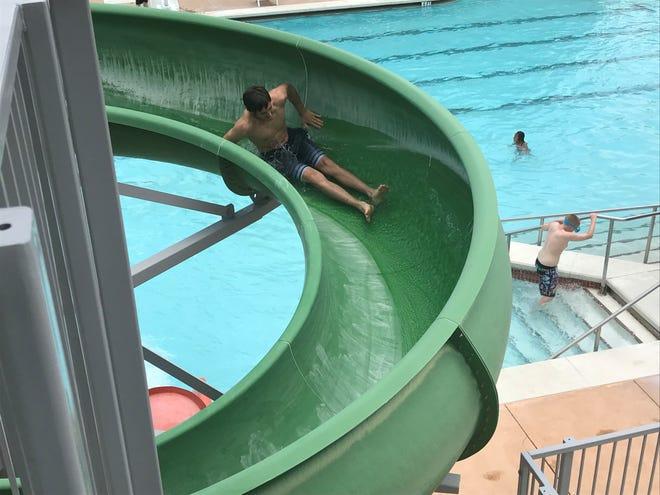 Dylan Narramore goes down a green slide at Municipal Pool Saturday, May 25, 2019.