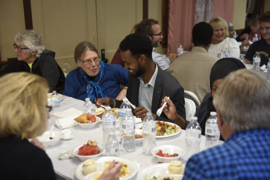 Abdi Daisane (center) talks with others over food at an iftar hosted by the Islamic Center of St. Cloud on Friday, May 24, 2019.