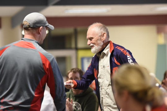 Phil Davis, 73, receives a medal in his age division at the awards ceremony for the Apple Duathlon in Sartell Middle School. Davis, from Tennessee, competed six years after having a stroke.