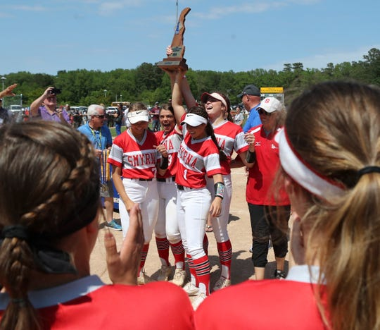 Smyrna players hold the championship trophy high after the Eagles defeated Caravel 1-0 in the 2019 DIAA Softball Tournament final in Roxana.