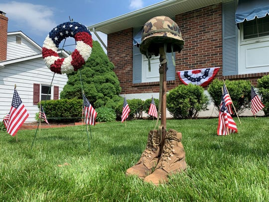 A shrine, built with Army surplus store items, is the centerpiece of Bill Smith's Pike Creek Memorial Day display. Ninety U.S. flags are spaced across his lawn, something he said draws regular appreciation from his neighbors.