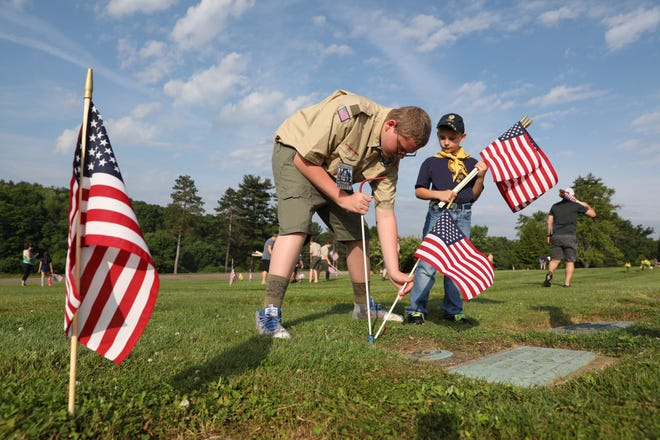 Boy Scout Andrew Matthews and Cub Scout Cooper Matthews place flags on the graves of veterans at Zanesville Memorial Garden Saturday morning.