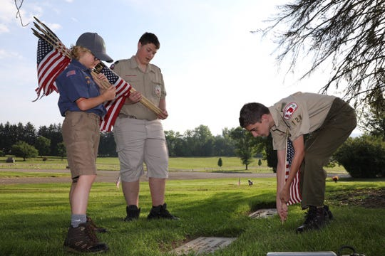 Boy Scouts Marcus Prindle and Thomas Milner, right, and Cub Scout James McCandlish place flags Saturday morning.