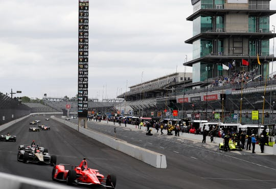 Marco Andretti, front, leads a pack of cars down the front straightaway into Turn 1 during practice for the 103rd Indianapolis 500.