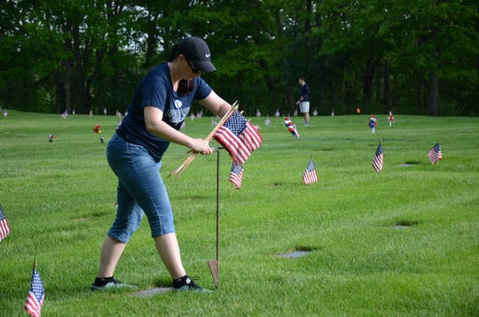 Jessica Brooks was one of hundreds of volunteers who placed flags at the cemetery on Saturday.