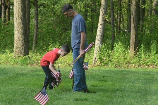 Ben Davis of Battle Creek and his son, Henry, place a flag at a grave on Saturday.