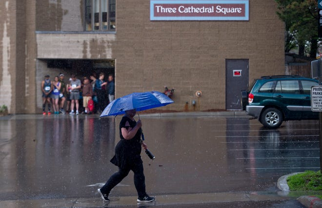 A pedestrian walks up Cherry Street beneath an umbrella as runners and spectators wait out a weather delay at the Vermont City Marathon on Sunday morning, May 26, 2019.