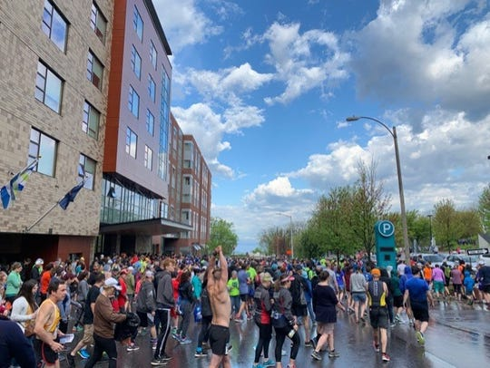 Vermont City Marathon runners retreat from the start at Battery Park to find shelter at the Cherry Street Garage on the morning of the Sunday, May 26, 2019. The 7 a.m. start time was delayed due to a storm.