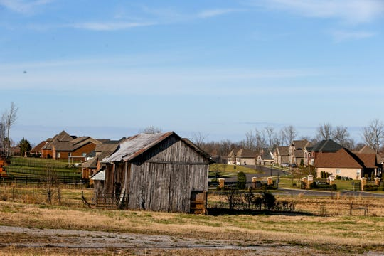 Fresh subdivisions can be seen in the distance past an old barn that still occupies a small patch of farmland along Madison Street in Clarksville, Tenn.