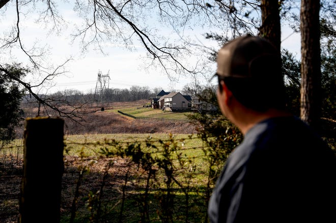 Alex Ponce de Leon looks past the fence in his backyard at  a neighborhood built on the edge of agriculture-zoned land at the Ponce de Leon home in Clarksville, Tenn., on Monday, March 11, 2019. Ponce de Leon fears these developments have a lot to do with the laws outlawing chicken coops and could make flooding more severe by allowing runoff waters to quickly flow downhill towards the streams and lakes in Montgomery County. Ponce de Leon moved to the county to escape city and suburban life but fears its rapid expansion.