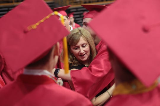 City High Language Arts teacher Robin Fields gets a hug from students before commencement ceremonies for the Iowa City High School graduating class of 2019 at Carver-Hawkeyes Arena in Iowa City on Saturday evening, May 25, 2019.